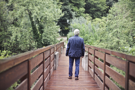 Aged man walking in a natural context