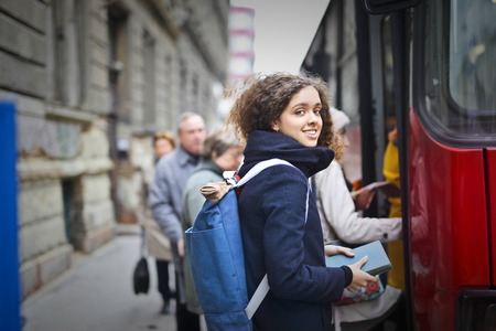 Girl with a backpack going on a bus