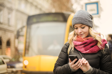 Girl using a smartphone at a bus stop