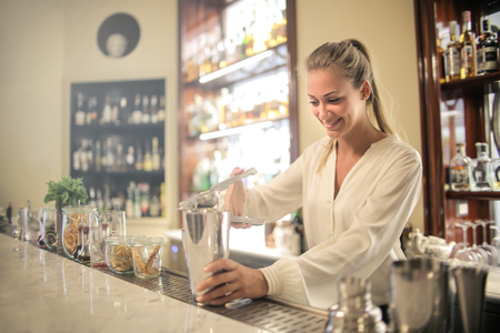 Girl preparing a drink in a bar Imagens
