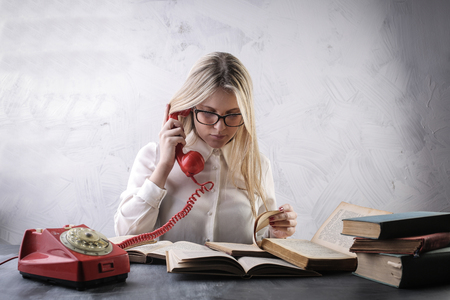 woman with books and a vintage telephone