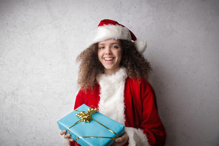 Girl dressed as Santa Claus with a present