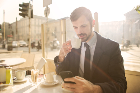 Businessman drinking some coffee and using a smartphone