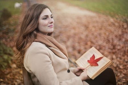 公園で本を持つ少女 写真素材