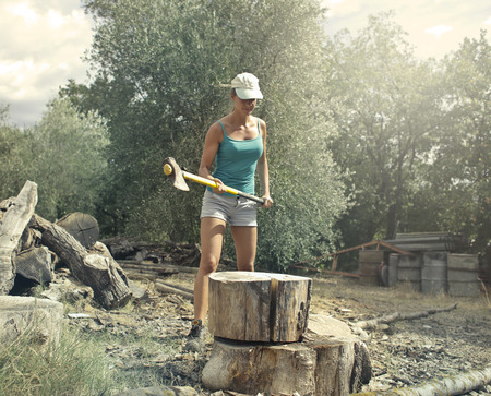 Girl cutting a trunk with an ax