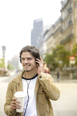 Guy listening to music and drinking outdoor