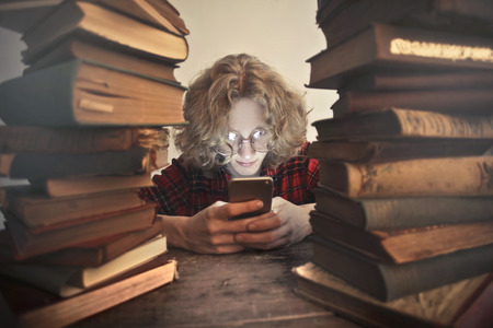 Guy with a smartphone surrounded by books