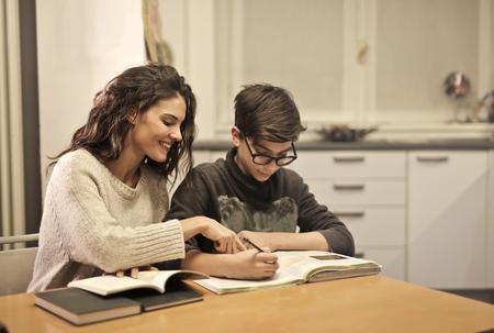 Dziewczyna pomaga dziecku w odrabianiu prac domowych