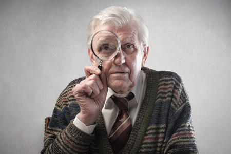 Aged man looking through a magnifying glass