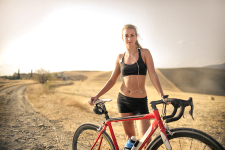 Sporty girl with a bike in the countryside
