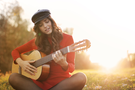 Girl playing acoustic guitar outdoor