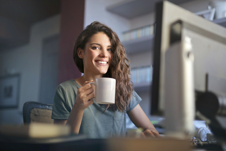 Girl using a computer and drinking some tea