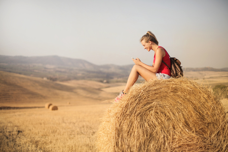 Girl sitting on a ball and using a smartphone