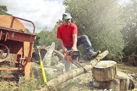Landbouwer die een boomstam op het platteland snijdt Stockfoto