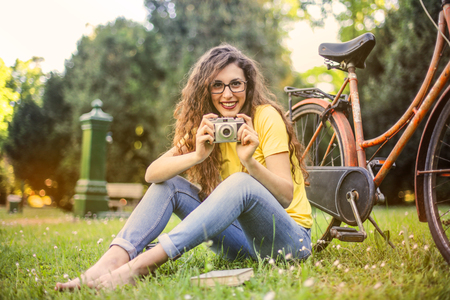 Happy girl in a park with a bike and a camera