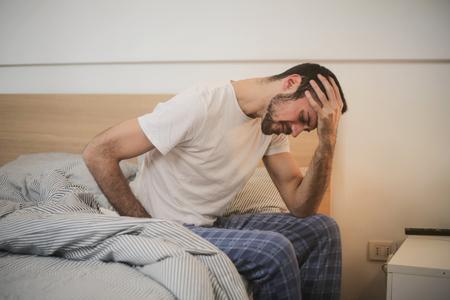 그의 침대에 앉아 pyjama에 피곤한 남자