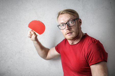 Guy with a red t-shirt playing table tennis Stock Photo