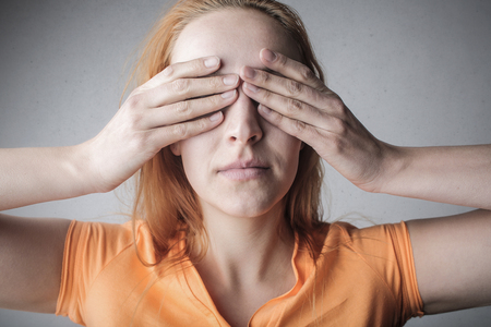 Woman covering her eyes with hands Stock Photo
