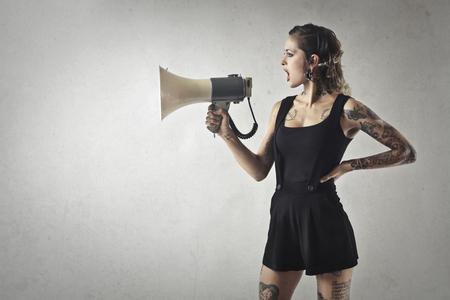 Portrait of a tattooed girl with a megaphone
