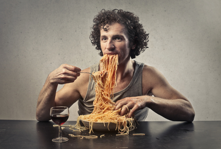 Portrait of a man eating spaghetti 免版税图像
