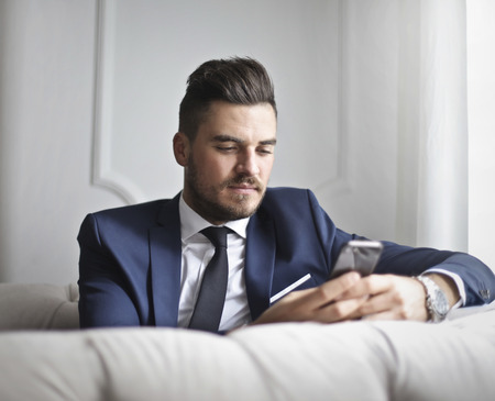 Man with phone on a sofa