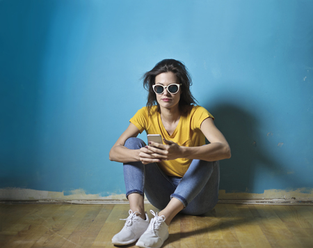 Yung woman with a smartphone sitting in front of a blue wall