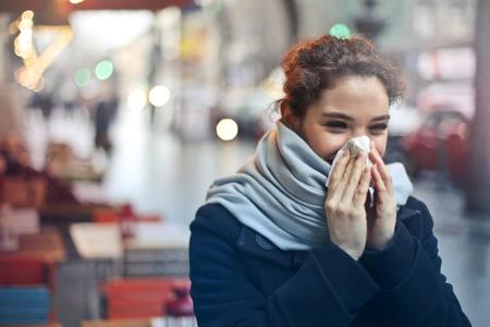 girl blowing her nose outdoor
