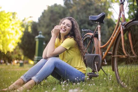 Happy girl in a park with a bike