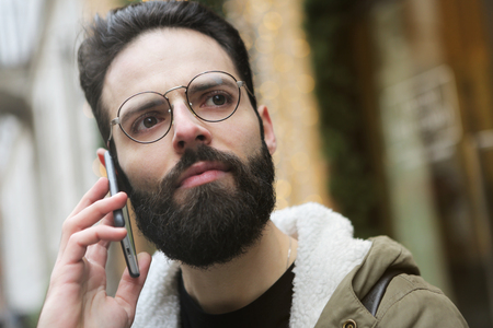 Bearded man talking to the phone outdoor Stock Photo