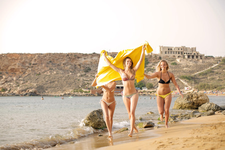 Three happy girls in bikini running on a beach