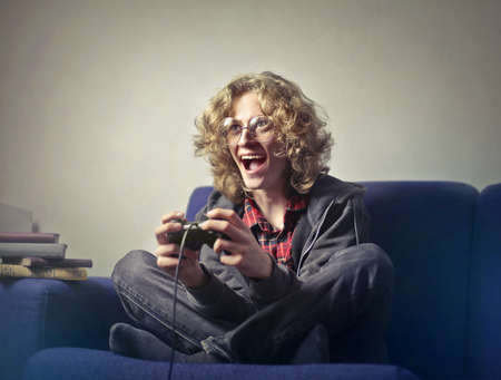Guy playing video games sitting on a sofa