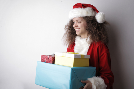 Girl dressed as Santa Claus with presents