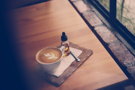 style: Latte coffee on wood table in vintage style.