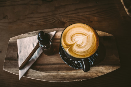 cup of coffee top view suface heart shape in wooden background design