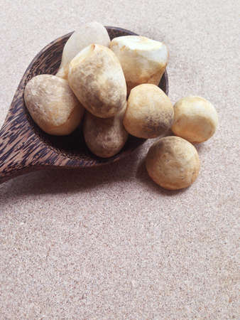 Straw mushroom with wooden spoon on plywood background