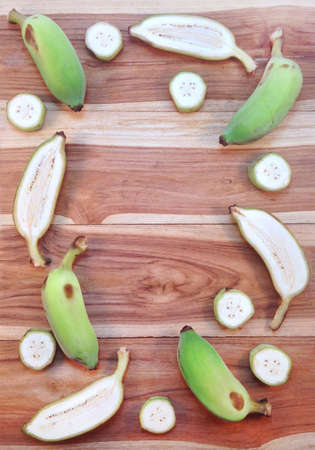 Green cultivated banana and piece of slices on wooden background