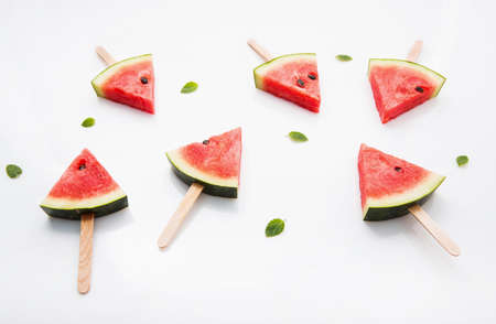 Watermelon slice popsicles and paper mint on white wooden background. Stock Photo