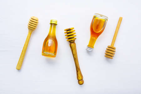 Honey wooden dipper and little honey bottle on white wooden background.