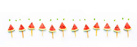 Watermelon slice popsicles and paper mint on white wooden background. Banco de Imagens