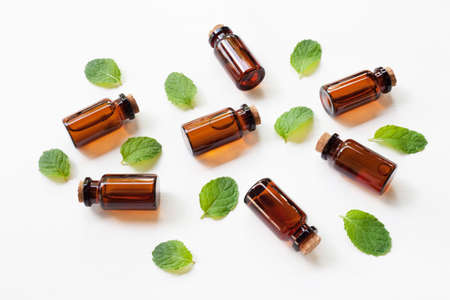 Holy Basil Essential Oil in a Glass Bottle with leaves on white background.