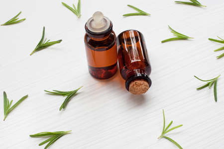 Rosemary essential oil with fresh leaves on white background.