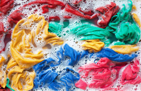 Color clothes soak in water with washing powder, before washing. Stock fotó