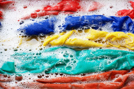 Color clothes soak in water with washing powder, before washing. Stock Photo