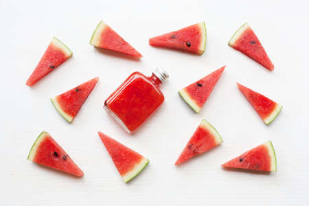 Bottle of fresh watermelon juice with  watermelon pieces  on white. Stockfoto