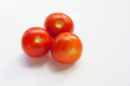 Three red  tomatoes on a white background.