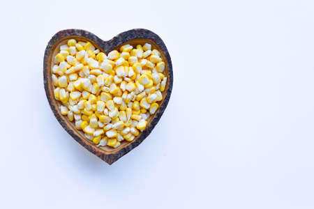 Corn seeds in wooden heart shape dish on white background Фото со стока