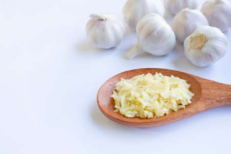 Fresh chopped garlic on wooden spoon with garlic head on white background 版權商用圖片