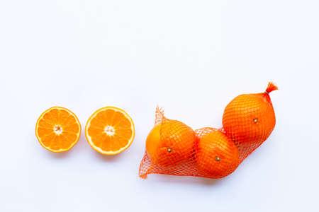 High vitamin C. Orange in net bag with ripe half of orange on white background. Copy space