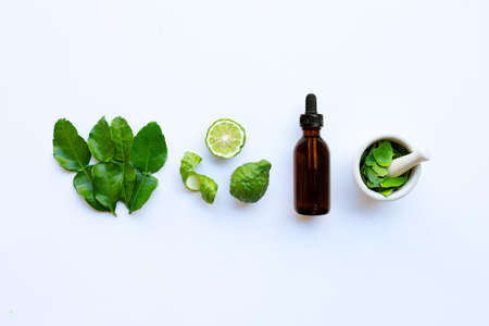 Bottle of essential oil and  fresh kaffir lime or bergamot fruit with leaves isolated on white background. Stock Photo