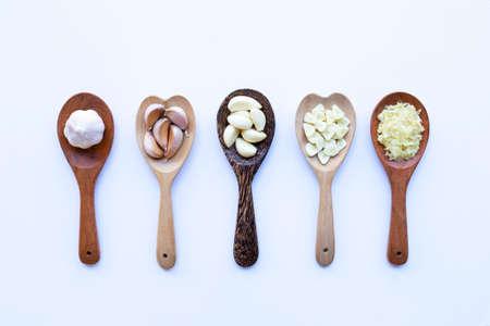 Garlic on wooden spoon on white background
